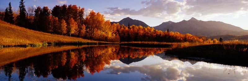 Красный осенний лес на фоне гор